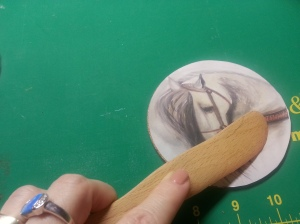 Use a burnishing tool to remove bubbles as you secure image to coaster.