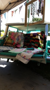 Selling from the back of an Aqua 1960 Chevy station wagon